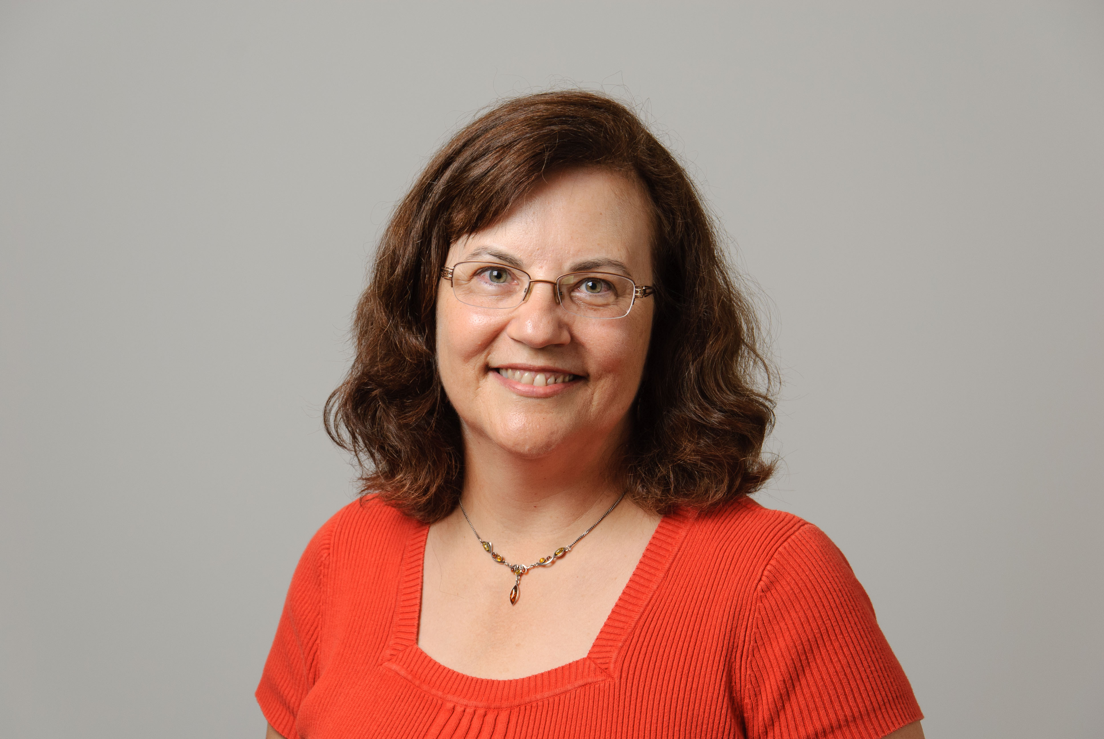 Woman with brown hair and glasses wearing an orange top